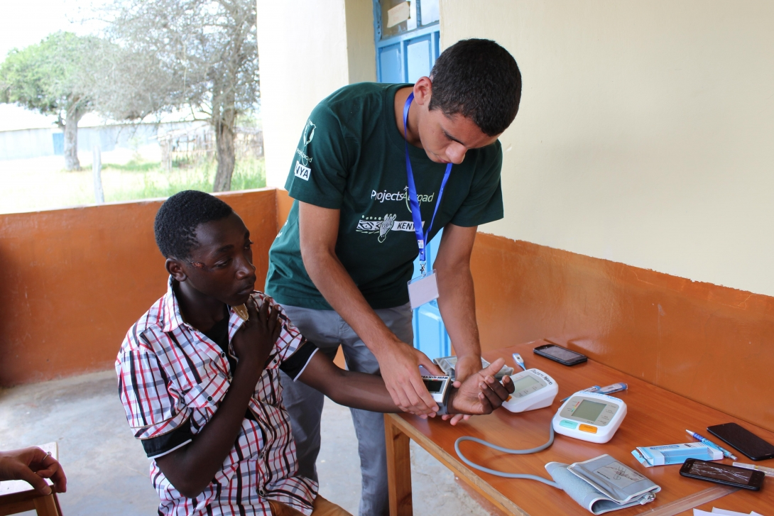 A teenager measuring a patient's blood pressure during his medical project for high school students.